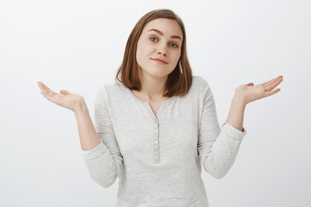 I do not care. Portrait of carefree pleased and calm good-looking woman in trendy outfit shrugging tilting head and smiling careless being clueless and uninterested over white background