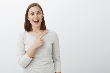 Waist-up shot of enthusiastic pleasant young european woman with short brown hair smiling broadly telling interesting story about copy space pointing at upper right corner over grey wall Stock Photo