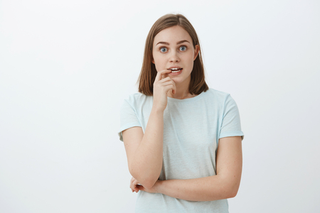 Girl eager to know end of story dying from excitement and interest. Portrait of curious enthusiastic and thrilled good-looking woman tv series fan biting fingernail and staring focused at camera Stock Photo