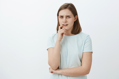 Girl facing tough decision thinking and hesitating biting finger while frowning looking intense and perplexed having troubles and no plan in mind, posing concerned against grey wall