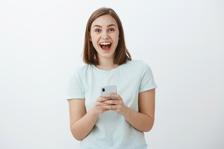 Amazed and excited attractive young european female model smiling broadly from great news received via internet holding smartphone gazing at camera thrilled and delighted posing against white wall Stock Photo