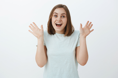 Girl being excited and surprised seeing friend unexpectedly raising palms near shoulder gasping and smiling joyfully from amazement and positive emotions standing in trendy t-shirt over gray wall Stock Photo