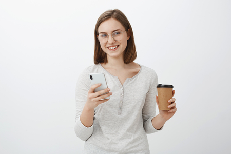 Just sec need answer. Charming carefree nice european woman in glasses holding paper cup with coffee drinking beverage enjoying talk with boss and typing message in smartphone over gray wall