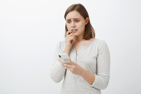 Girl feeling nervous sending money via app to wrong person biting fingernail frowning staring anxiously at smartphone screen being shocked and scared of bad consequences of action over gray wall