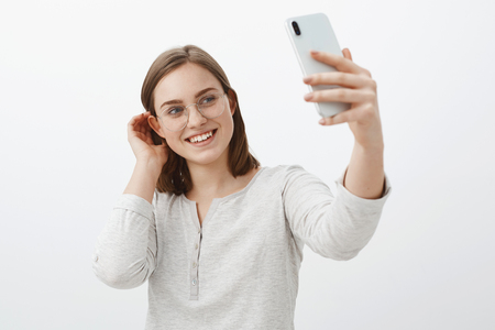 Cute gentle girlfriend making selfie to send on dating app waiting for true love come flicking hair strand behind ear and smiling tenderly at smartphone screen standing feminine over gray wall