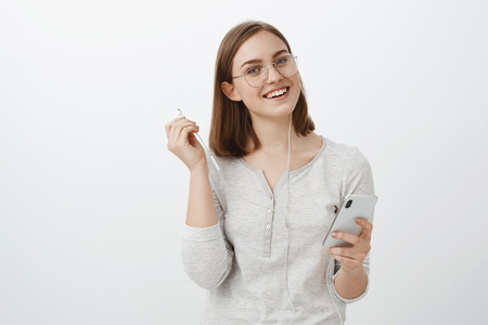 Waist-up shot of cheerful charming caucasian girlfriend in trendy glasses holding smartphone taking off earphones and gazing carefree at camera listening favorite song interrupting to talk with friend