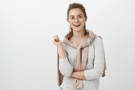 Waist-up shot of amused sociable good-looking european woman with combed hair in glasses and pullover tied over neck gesturing during talk and smiling broadly feeling interested in conversation