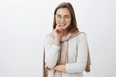 Girl looking at curious guy trying turn attention biting finger and smiling intrigued gazing left with interest and desire having mysterious delightful idea standing over gray background