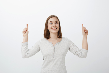 Girl likes counting start. Portrait of charming dreamy young woman with short brown haircut smiling joyfully looking and pointing up while enjoying great summer night posing against grey wall
