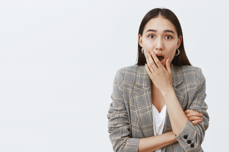 Gosh, is it true. Indoor shot of shocked and excited attractive dark-haired female in trendy jacket, dropping jaw and covering opened mouth, being impressed and surprised, hearing rumor or gossip