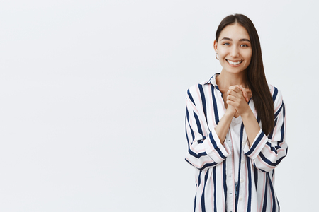 Girl looking with caring and admirable eyes at camera, being thrilled and charmed with pleasant gift, clasping hands over chest and smiling with happiness, standing in striped blouse over gray wall