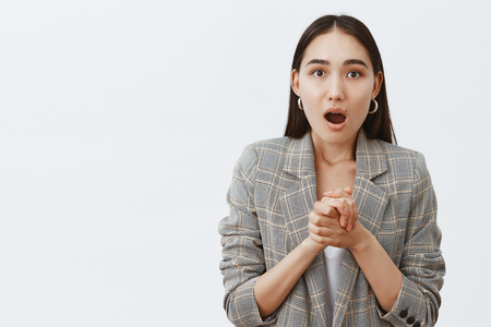 Wow, amazing, tell me more. Portrait of stunned and shocked good-looking asian girlfriend in jacket over t-shirt, clasping hands over chest and gasping from excitement and amazement Stok Fotoğraf