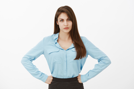 How could you disappoint me. Displeased unhappy european female in blue blouse, holding hands on hips and frowning, being disappointed or offended, complaining, blame colleague for bad work