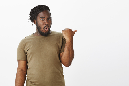 Guy impressed with friends new car. Fascinated surprised attractive dark-skinned boyfriend in military t-shirt, raising thumb and pointing right with amazed expression, discussing copy space