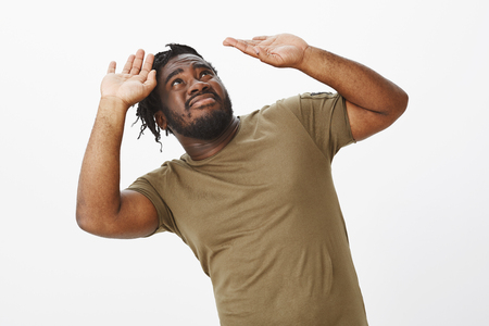 Guy trying to bear weight of responsibility. Displeased uncomfortable dark-skinned male model in olive t-shirt, bending backwards, looking and raising palms high to protect from falling item Imagens