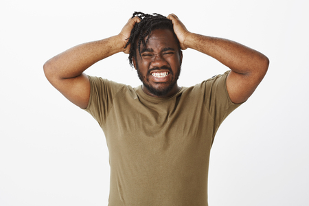 Guy cannot hold negative emotions inside. Depressed desperate african american man in olive t-shirt, holding hands on hair, grimacing with clenched teeth, feeling pain in soul or being angry
