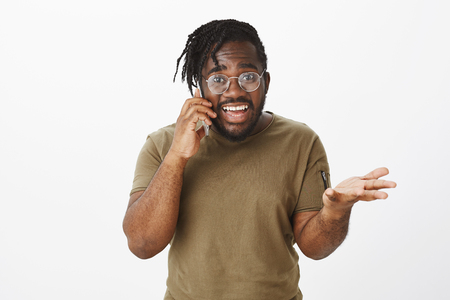 Waist-up shot of energetic impressed attractive dark-skinned man with stylish haircut, raising palm and shaking hand while talking on smartphone, gazing at camera during passionate conversation