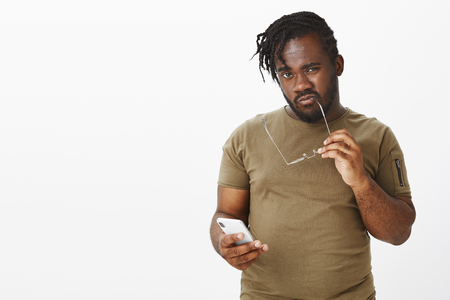 Waist-up shot of curious doubtful young african plump man in casual outfit, sucking rim of glasses and staring at camera with intrigued smart expression, holding smartphone, reconcireding plan