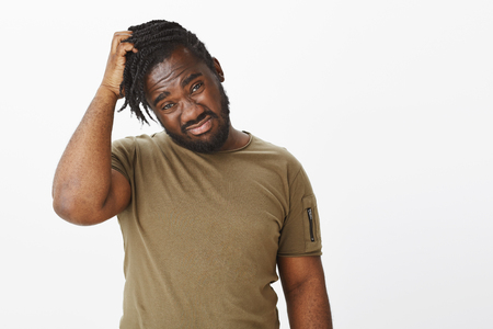 Waist-up shot of unsure and uncertain african-american guy scratching head and staring displeased at camera, being confused or stuck while making decision, having no idea what to do over grey wall