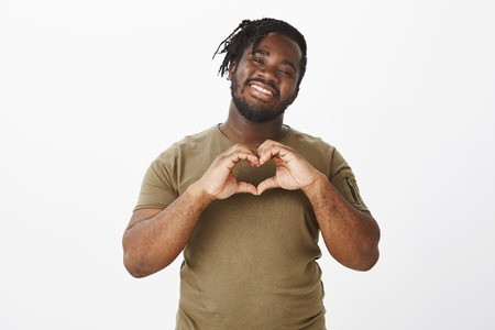 Sharing love and warm emotions with girlfriend. Portrait of happy carefree african male friend in olive t-shirt, smiling joyfully while showing heart gesture over chest, being passionate and flirty