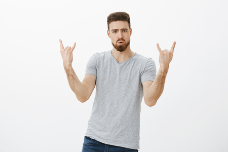 Let us rock this party. Portrait of enthusiastic handsome and stylish male model with beard and moustache showing rock-n-roll gesture pouting and frowning enjoying concert and music against white wall Reklamní fotografie