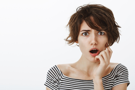Portrait of shocked and worried cute female with short stylish haircut, frowning and gasping with dropped jaw, holding hand near mouth, feeling nervous hearing terrible news or witnessing accident 版權商用圖片