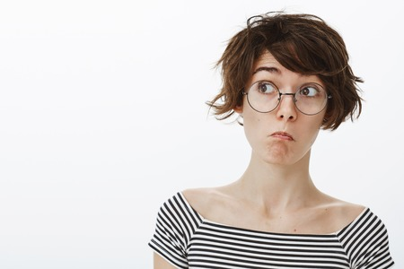 Wow, it is amazing but unexpected. Impressed cute and funny girl in round glasses with stylish short haircut, pulling face in not bad emotion, looking left curiously, standing pleased over grey wall