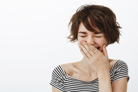Stop you making me laugh. Portrait of joyful happy cute girl with messy short hair and stylish striped cropped top, laughing out loud with closed eyes, chuckling and covering mouth with palm