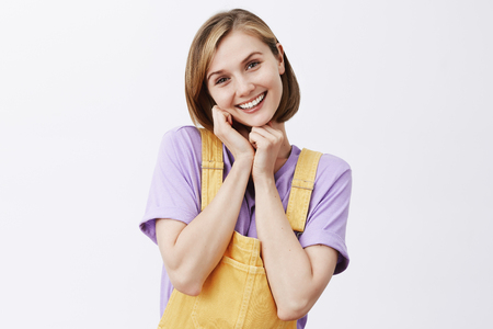 Oh you are so sweet. Charmed and pleased tender girlfriend with blond short haircut wearing yellow dungarees, tilting head and holding hands near face, being touched and gazing with admiration