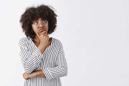 Portrait of thoughtful dreamy and focused cute dark-skinned female with curly hair pouting holding hand on chin and gazing at upper right corner while thinking and making up idea or plan