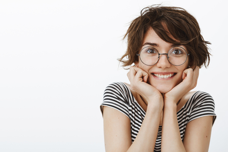 Waist-up shot of feminine cute woman with short brown haircut in glasses, smiling broadly, leaning head on palms, gazing with interest and curiousity at camera, listening carefully interesting story