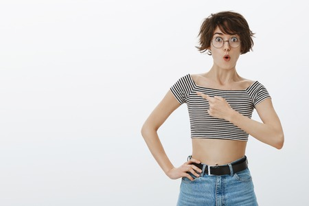 Very interesting, what is it. Portrait of curious good-looking woman with short hairstyle in round glasses and striped cropped top, folding lips saying wow while pointing left with forefinger