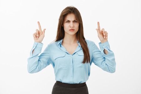 Woman do not like new design of house. Portrait of disappointed displeased charming woman in blue blouse, pointing up with raised index fingers, frowning and sulking, being offended or insulted