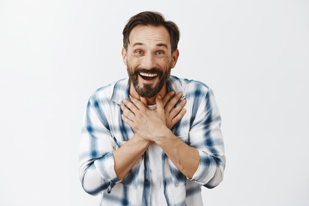 Guy feeling touched and pleased, happy family remember what he want on b-day. Charmed kind and joyful adult bearded man in checked shirt, holding palms on chest and smiling, gasping from surprise