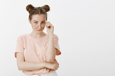 Are you sure about it. Portrait of uncertain beautiful female with buns hairstyle and freckles, taking off glasses and staring doubtfully at camera, being unsure, expressing hesitation and interest