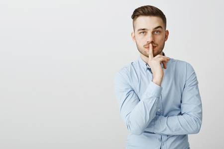 Waist-up shot of smart self-assured attractive businessman with bristle in blue office shirt making shh gesture shushing at camera with index finger over mouth telling partner keep company secret safe