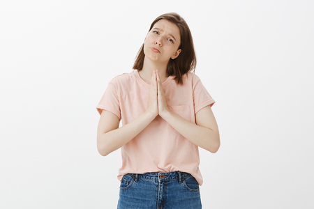 Please mom buy me new phone. Charming emotive woman in trendy clothes, tilting head, folding lips and frowning while holding hands in pray, wanting something, asking help or apology, begging for favor Standard-Bild