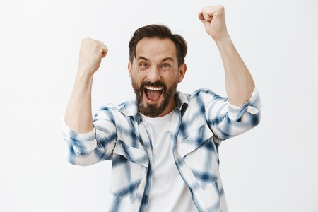 Yeah come on we will win. Portrait of happy joyful and emotive mature european guy with beard and dark hair, raising fists high and yelling
