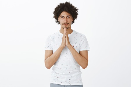 Good-looking handsome hispanic buddhist, holding hands in pray and smiling at camera with calm and peaceful expression, making namaste gesture while relaxing and meditating, praying over gray wall