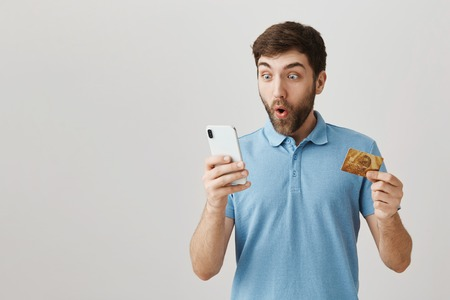 Online shopping and advertising concept. Surprised excited man holding smartphone and credit card while paying for some goods and being happy of cashback feature. Guy bought goods with huge discount