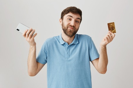 Pleased and happy european guy shrugging while holding smartphone and credit card, smiling and standing over gray background. Man is pleased how simple he can now pay for his needs