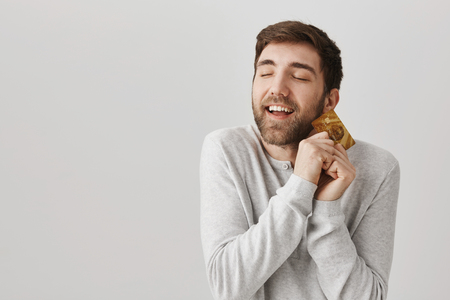 Positive and excited european guy with beard hugging credit card with pleased expression and closed eyes, standing over gray background. Man is happy he finally received payment. Stockfoto