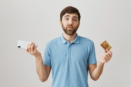 Studio shot of casual caucasian male with beard, holding smartphone and expensive smartphone, being sad while standing over gray background. Account is empty but at least guy has new phone Stok Fotoğraf