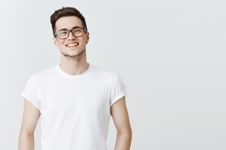Waist-up shot of pleasant and friendly-looking handsome happy young guy in glasses smiling broadly as standing over gray copy space carefree and joyful living fulfilled life, enjoying conversation Фото со стока