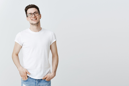 Successful pleased european IT guy celebrating signing good deal with investors, standing proudly smiling broadly, laughing, holding hands in pockets, wearing glasses and t-shirt over grey wall Reklamní fotografie - 110444500