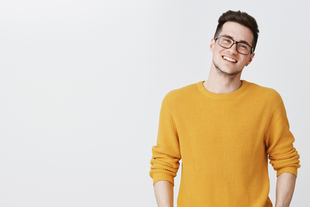 Waist-up shot of happy and delighted handsome young man in glasses and yellow sweater tilting head, smiling and laughing as looking friendly at camera on right side of copy space over gray background Reklamní fotografie