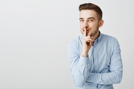 Guy about tell amazing rumor asking keep secret. Enthusiastic good-looking male with bristle, stylish hairstyle in blue office shirt smiling intrigued making shh gesture with index finger over mouth