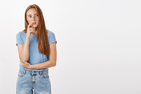 What if I order junk food. Thoughtful concentrated and curious redhead woman in blue t-shirt and jeans biting finger intrigued looking right while thinking having desire or interest in something Stock fotó