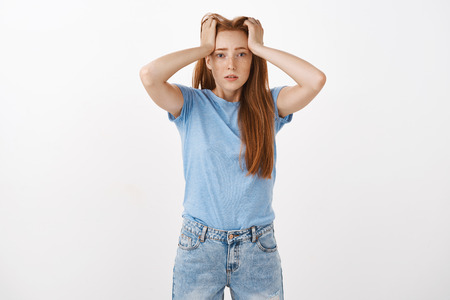Gosh hate being student. Portrait of cute redhead woman under pressure holding hands on head with perplexed and troubled look being tired and fed up of paper work sighing over gray background