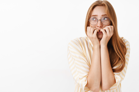 Waist-up shot of worried panicking cute and timid insecure redhead girl in glasses looking up trembling from fear biting fingernails shaking feeling scared over gray background